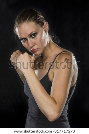 Half Body Shot of a Young Female Fighter with Tattoo, Looking Fierce at the Camera Against Black Background. - stock photo