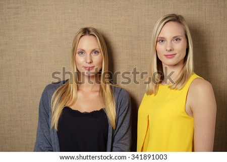 Half Body Shot of Two Confident Young Women Looking at the Camera Against Brown Wall Background. - stock photo