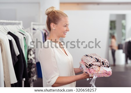 Half Body Side View Shot of a Pretty Young Woman Holding a Pile of Clothes to Buy Inside the Clothing Store - stock photo