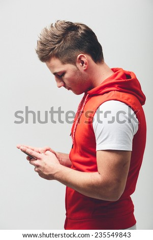 Half Body Side View Shot of Young White Man in Red Jacket with Hood Busy Texting Using Mobile Phone. Isolated on Light Gray Background. - stock photo