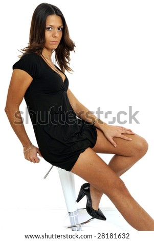 Half body view of young woman sitting on a stool in chic wear. Isolated on white background. - stock photo