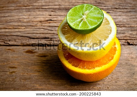Half Cut Sliced Group of Citrus fruits Fresh Lemon, Green Lime and Orange on Wood Table Background, Rustic Still Life Style. - stock photo