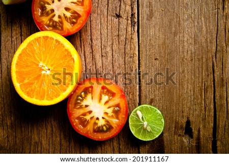 Half Cut Sliced Group of Citrus fruits Fresh Lemon, Green Lime, Orange and Red Tomato on Wood Table Background, Rustic Still Life Style. / Concept and Idea of Food Decoration and Food Background. - stock photo