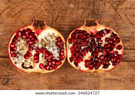Half-cutted fresh grenadines on rustic wooden table - stock photo
