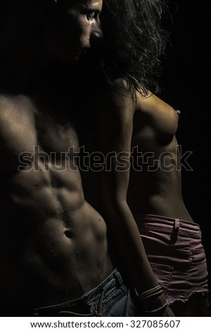 Half dressed sexual passionate pair of two people man with beautiful muscular body touching young woman with bare breast standing in studio close to each other on black background, vertical picture - stock photo