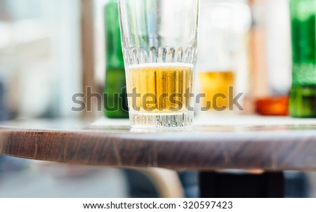 Half empty glasses of beer on the table, blurred background - stock photo