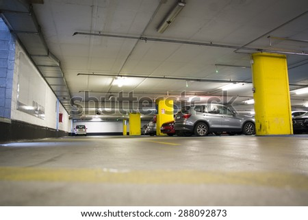 Half empty underground garage or parking lot, with a few cars - stock photo