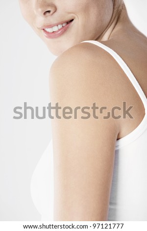 Half face and shoulder detail of a beautiful young woman. - stock photo
