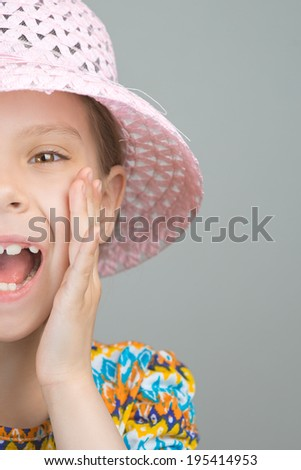 Half face of beautiful young girl shouts loud voice, on gray background. - stock photo