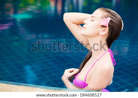 half face portrait of beautiful woman in luxury pool - stock photo