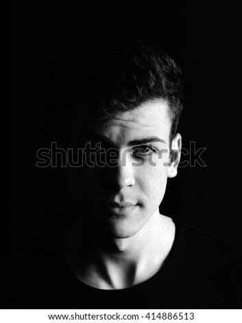 half-face young man portrait in low-key  - stock photo