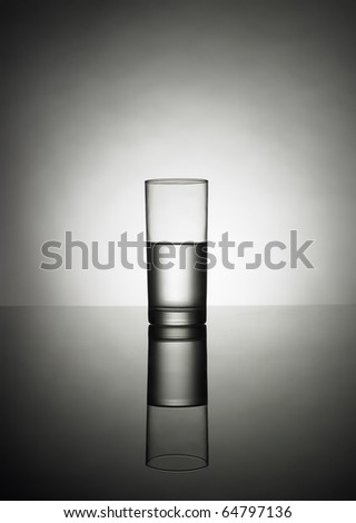 half glass of water on a reflexion - stock photo