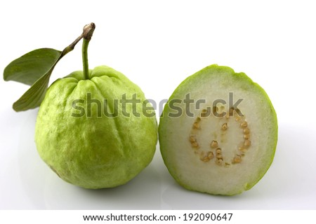 Half guava and slices with the complete one on white background - stock photo