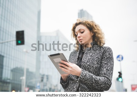 Half length of a young beautiful caucasian contemporary businesswoman walking through the streets of the city using a tablet looking the screen - technology, network, business, finance concepts - stock photo