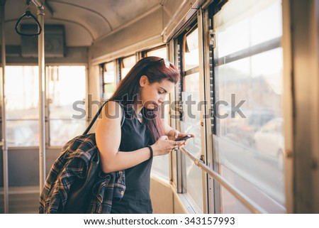Half length of a young beautiful reddish brown hair caucasian woman using a smartphone on a tram - technology, social network, communication concept - looking down the screen - stock photo