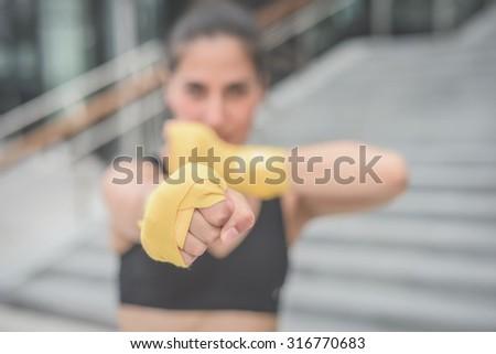 Half length of a young handsome caucasian brown hair boxer woman boxing, looking in camera, focus on fist - sportive, training, healthy, fitness concept - stock photo