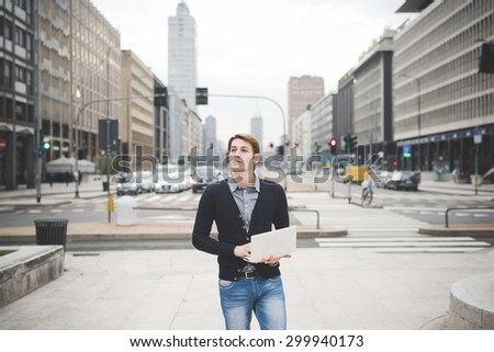 Half length of a young handsome caucasian contemporary businessman standing on the street using a notebook overlooking - technology, network, business, finance concepts - stock photo