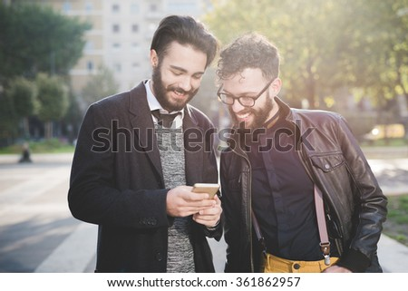 Half length of two young handsome caucasian bearded brown hair businessmen standing in the city backlight, looking downward and tapping the screen of smartphone - business, technology, work concept - stock photo