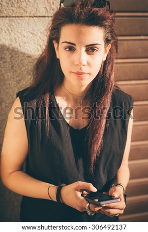 Half length of young beautiful caucasian reddish brown hair girl using smartphone looking in camera - carefreeness, freshness, youth concept - dressed with blue jeans, black shirt - stock photo