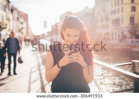 Half length of young beautiful caucasian reddish brown hair girl walking using smartphone looking down the screen - carefreeness, freshness, youth concept - dressed with blue jeans, black shirt - stock photo