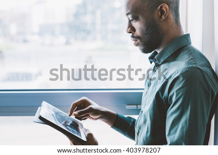 Half length of young handsome afro businessman near a window holding a tablet, looking down and tapping the screen - business, working, job concept - stock photo