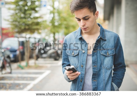 Half length of young handsome alternative dark model man in town using smartphone handhold, looking down the screen - technology, sharing, social network concept - stock photo