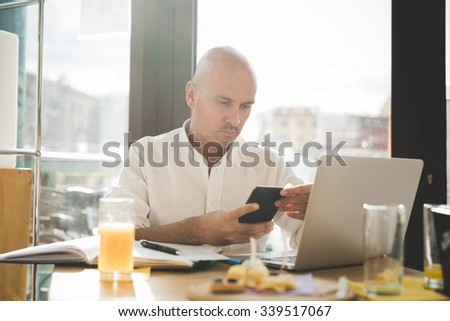 Half length of young handsome caucasian bald business man sitting in a bar using a laptop leaning on his knees, looking downward the screen, pensive - working, thoughtful, busy concept  - stock photo