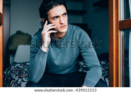 Half length of young handsome caucasian brown hair man sitting talking smartphone, overlooking pensive - business, working, multitasking concept - stock photo
