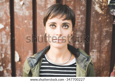 Half length of young handsome caucasian brown straight hair woman posing leaning against a wall, looking straight, pensive - serious, thoughtful concept - stock photo