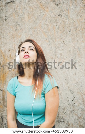 Half length of young handsome caucasian reddish straight hair woman leaning against a wall listening music with headphones, looking upward, pensive - thinking future, thoughtful concept - stock photo