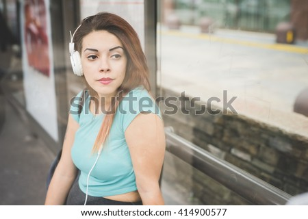 Half length of young handsome caucasian reddish straight hair woman sitting at the bus stop listening music with headphones, overlooking left, pensive, view behind a window - stock photo