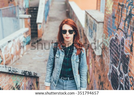 Half length of young handsome caucasian redhead straight hair woman posing on a staircase in the city, wearing sunglasses, looking in camera pensive - serious, thoughtful concept - stock photo