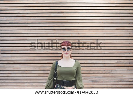 Half length of young handsome redhead caucasian woman, leaning against a wall, looking in camera, smiling - pin up, carefree concept - stock photo