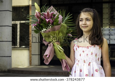 Half-length portrait eight-year girl with the bouquet in the hands - stock photo