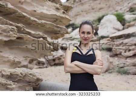 Half length portrait of a beautiful female jogger posing while taking break between intense exercising outdoors, young charming fit women relaxing after her workout outside in a cloudy summer day - stock photo