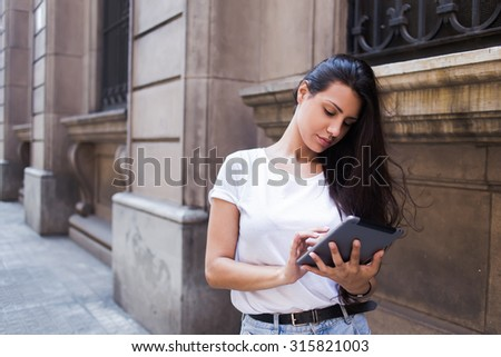 Half length portrait of a charming latin woman viewing photos on her digital tablet computer while standing on the street in summer day, beautiful hipster girl using on touch pad in urban setting - stock photo