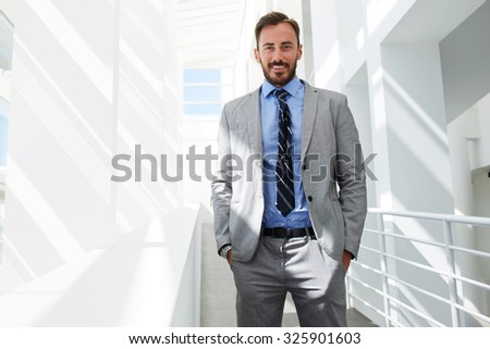 Half length portrait of a happy smiling successful men manager posing while standing on the corridor of office building, cheerful smart businessman dressed in elegant suit resting after conference  - stock photo