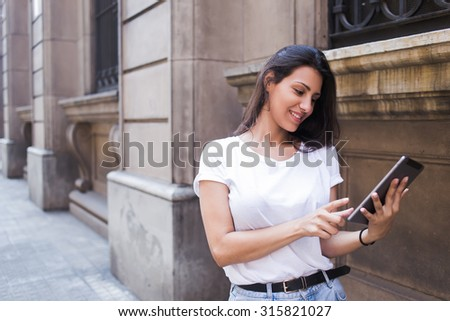 Half length portrait of a smiling latin woman looking photo on her digital tablet computer while walking on the street, happy female tourist using touch pad for navigation during summer vacation trip - stock photo