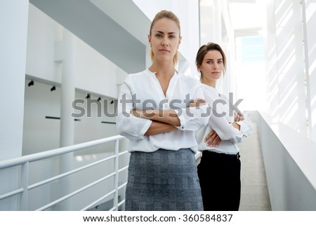 Half length portrait of a successful businesswoman which want to be first posing while her partner standing at the side, team of female managers with crossed arms waiting for meeting with competitors - stock photo