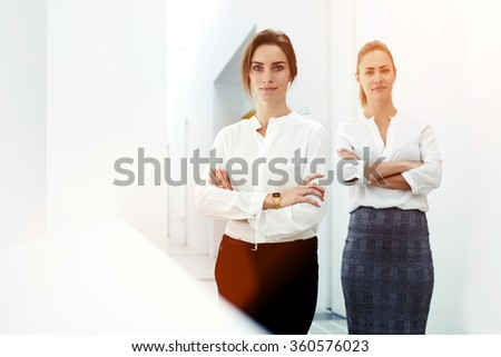 Half length portrait of a two young skilled female dressed in elegant clothes posing in hallway big company, attractive women professional workers standing with crossed arms in modern office interior  - stock photo