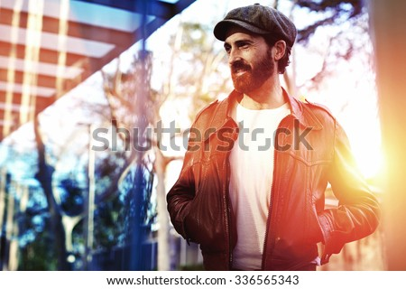 Half length portrait of an adult bearded hipster man dressed in classy stylish clothes waiting for someone on the street, beautiful male with trendy look standing in urban setting in autumn day  - stock photo