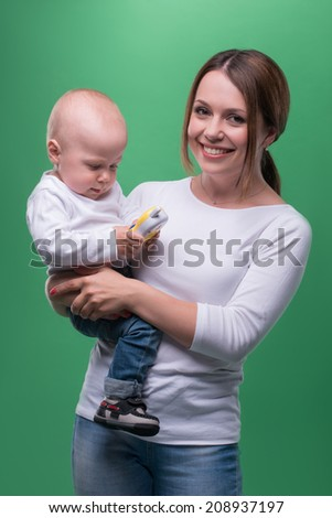 Half-length portrait of attractive caucasian mother holding toddler son with toy phone and smiling ta camera, white T-shirts and jeans, role-playing, isolated on green - stock photo