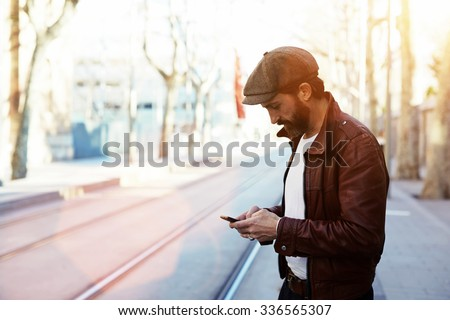 Half length portrait of bearded hipster man dressed in stylish clothes chatting on cell telephone while standing in the street, glamorous male with cool style use smart phone during strolling outdoors - stock photo