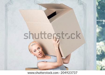 Half-length portrait of beautiful smiling blonde wearing nice grey vest and holding empty box on her shoulder and showing us her strength - stock photo