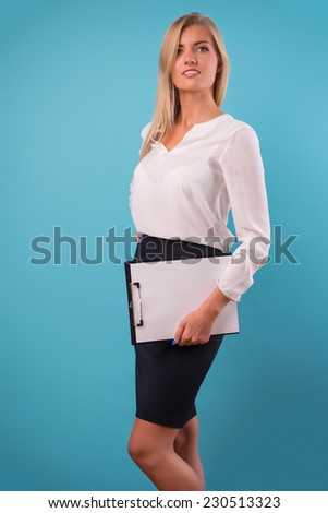 Half-length portrait of beautiful smiling business lady wearing white classic blouse and black skirt standing aside holding a folder for copy place. Isolated on blue background - stock photo