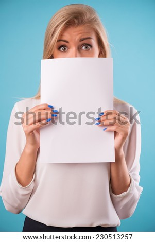 Half-length portrait of beautiful smiling business lady wearing white classic blouse standing hiding behind the white sheet of paper for copy place. Isolated on blue background - stock photo