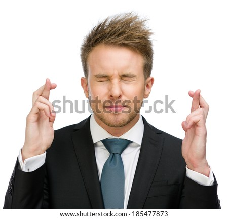 Half-length portrait of businessman with fingers crossed and eyes closed, isolated on white - stock photo