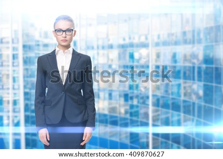 Half-length portrait of businesswoman wearing glasses with black frame, blue background. Concept of leadership and success - stock photo