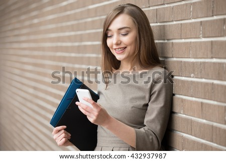 Half length portrait of cheerful young woman standing in the street beside brick wall, sending message on smartphone. Happy beautiful caucasian woman using mobile phone, making call, looking at screen - stock photo