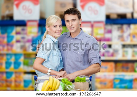 Half-length portrait of couple in the shopping center with cart full of food. Concept of consumerism and healthy food - stock photo